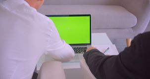 Closeup back view portrait of two businessmen using laptop with green screen and shaking hands in the office indoors.  stock footage