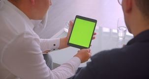 Closeup back view portrait of two businessmen using tablet with green chroma key screen having a meeting sitting in. Armchairs in office indoors stock footage