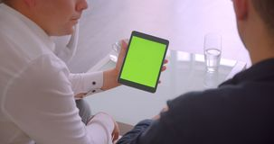 Closeup back view portrait of two businessmen using tablet with green chroma key screen having a meeting sitting in. Armchairs in office stock video footage