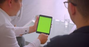 Closeup back view portrait of two businessmen using tablet with green chroma screen having a meeting sitting in. Armchairs in office indoors stock footage