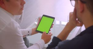 Closeup back view portrait of two businessmen using tablet with green screen having a meeting sitting in armchairs in. Office indoors stock video