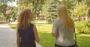 Closeup back view portrait of two pretty caucasian female friends walking in park outdoors stock video footage
