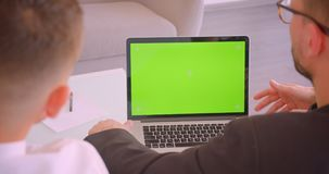 Closeup back view portrait of two successful caucasian businessmen using laptop with green chroma key screen in the. Office indoors stock footage