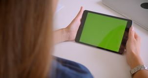 Closeup back view portrait of young attractive caucasian woman playing ad on tablet with green chroma key screen in. Office indoors stock video footage