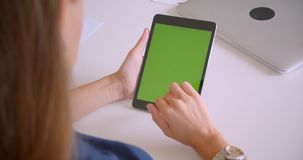 Closeup back view portrait of young attractive caucasian woman playing advertisement on tablet with green chroma key. Screen in office indoors stock video