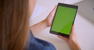 Closeup back view portrait of young attractive caucasian woman tapping on tablet with green chroma key screen in office. Indoors stock video footage