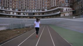 Closeup back view portrait of young attractive fit caucasian female jogging outdoors on the stadium in the urban city.  stock video