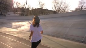 Closeup back view portrait of young attractive fit caucasian female jogging outdoors on the stadium in the urban city in. A warm spring day stock video footage