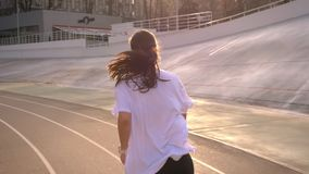 Closeup back view portrait of young attractive fit caucasian female with ponytail jogging outdoors on the stadium in the. Urban city stock video footage