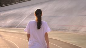 Closeup back view portrait of young attractive fit caucasian female with ponytail walking outdoors on the stadium in the. Urban city in a warm spring day stock video