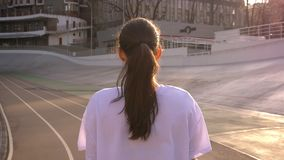 Closeup back view portrait of young attractive fit caucasian female with ponytail walking outdoors on the stadium in the. Urban city stock video