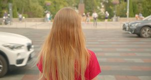 Closeup back view portrait of young blonde long haired beautiful female standing by road with cars passing by outdoors stock video footage