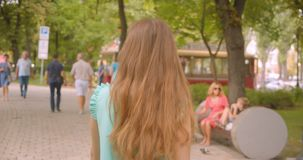 Closeup back view portrait of young long haired beautiful female walking in park outdoors stock footage