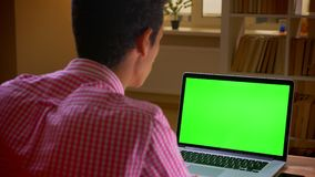 Closeup back view shoot of indian young businessman having a video call on the laptop with green chroma screen in the. Office indoors stock video