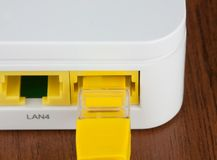 Closeup back of white wifi router LAN port with UTP patch cord inside. On the wooden table Stock Image