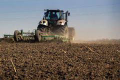 Closeup backside cultivator raises great dust on ploughed soil Royalty Free Stock Photo