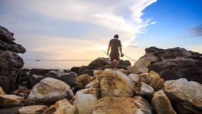 Closeup Backside Guy with Rods Walks on Stones to Sea at Sunset. Closeup backside view guy with rods walks on large stones on beach to sea water for fishing stock video footage