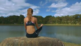 Girl Does Yoga Enjoys Scenery near River under Sun. Closeup backside view blonde girl does yoga and enjoys magnificent scenery near river under sunshine stock video footage