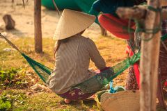 Backside Woman in Straw Hat Sits in Hammock in Vietnam Stock Photography