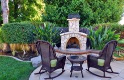 Closeup of backyard oasis. Outdoor oasis with stone fireplace Royalty Free Stock Photos