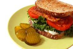 Closeup of a bacon, lettuce and tomato sandwich with pickles Royalty Free Stock Photography