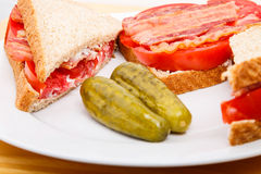 Closeup of Bacon and Tomato Sandwich with Dill Pickles. Fresh bacon and sliced tomato slices on a white plate with pickles royalty free stock image