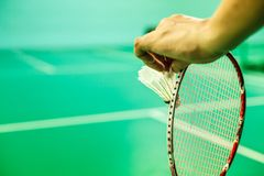 Closeup Badminton player hand holding the shuttle cock together with the racket, ready to serve position on the play green court w. Ith copy space Royalty Free Stock Image