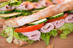 Ham and vegetables sandwich. Closeup of the baguette sandwich with ham, cucumber, tomato and lettuce Stock Photography