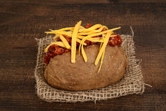 Closeup baked potato with chili and cheese. On burlap napkin Stock Image