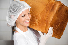 Closeup Of Baker Smiling While Carrying Big Bread Loaf Stock Image