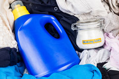 Closeup on baking soda with detergent and pile of dirty laundry. Royalty Free Stock Photos