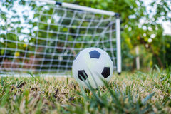 Closeup of ball and football goal in the back Royalty Free Stock Photography