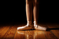 Closeup of Ballerina Feet In First Position. Closeup of a ballerina's feet in pointe shoes on a vintage, wood floor with black background. First position, flat royalty free stock photo