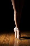 Closeup of Ballerina Legs. Ballerina en pointe on dark wooden floor with black background royalty free stock images