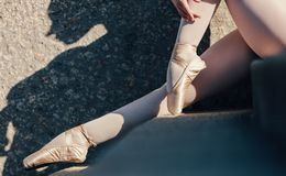 Close up of pointe shoes worn by female ballet dancer. Closeup of ballet dancer sitting outdoors. Ballet dancer wearing pointe shoes sitting on stairs stock image