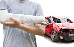 Closeup of bandaged arm with blue wrecked car. Over white background stock photography