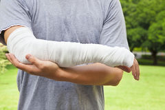 Closeup of bandaged arm with park background. Closeup of bandaged arm with tree and meadow background royalty free stock image