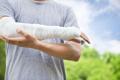 Closeup of bandaged arm in the park. Closeup of bandaged arm with blue sky in the park stock images