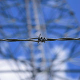 Closeup of Barbed Wire with Communications Tower in Background. Close-up detail of barbed wire with sunny, blue sky and radio tower in background Royalty Free Stock Photos