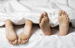 Closeup Of Barefeet In Bed. Closeup of a couple lying in bed barefeet Royalty Free Stock Photo