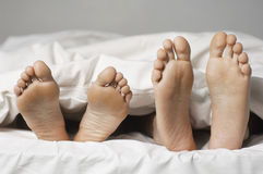 Closeup Of Barefeet In Bed. Closeup of a couple lying in bed barefeet Stock Photos