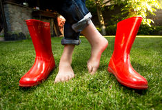 Closeup of barefoot girl standing on grass with red rubber boots Royalty Free Stock Photos
