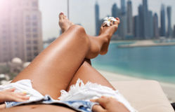 Closeup barefoot woman legs at the resort. Woman relaxing at terrace with beautiful city view Royalty Free Stock Images
