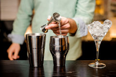 Closeup of bartender hands pouring drink into a jigger to prepare a cocktail Stock Photos
