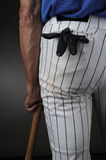 Closeup Baseball Player Leaning on Bat. Closeup of a baseball player seen from behind and leaning on a wood bat. Man is unrecognizable with a batting glove in Stock Image