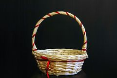 On a black background basket for gifts from wood fibers. Closeup of a basket with a handle of wood fibers with a festive ribbon for decoration of gifts, on a stock images
