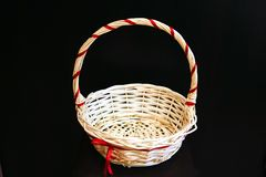 On a black background basket for gifts from wood fibers. Closeup of a basket with a handle of wood fibers with a festive ribbon for decoration of gifts, on a stock photography