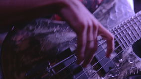 Closeup bassist playing the bass guitar. In concert stock footage