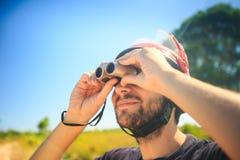 Closeup Man in Helmet Watches Sky with Binocular Stock Photography