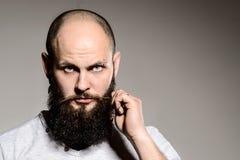 Closeup of bearded man touching his beard Stock Photography